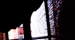 unscharf gehaltenes frauenportrait vor einem fenster, durch das eine alte ziegelmauer zu sehen ist. aufnahme: heidelberg, 30. januar 2005