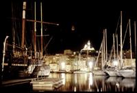 nächtlicher blick über den alten hafen von marseille hinauf zu notre dame de la garde, die im bildhintergrund gleissend hell angestrahlt ist. marseille, am 19. dezember 2005